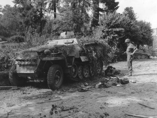 """Zniszczona kolumna 1. Dywizji Pancernej SS """"Leibstandarte SS Adolf Hitler"""". Na pierwszym planie - transporter opancerzony Sd Kfz 251/8. Kolumna została zniszczona bezpośrednim ogniem z 57-mm armaty ppanc sierżanta Rhyne'a Millera  z 30 Dywizjonu 120 Pułku US . Gdzieś we Francji."""