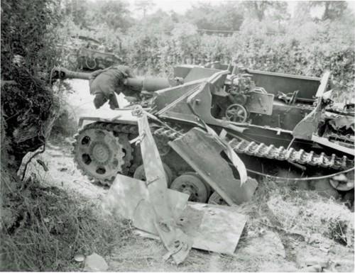 Niemieckie działo szturmowe StuG IIIF po eksplozji. Sądząc po stanie pojazdu, jest to wynik bezpośredniego trafienia pociskiem dużego kalibru (np haubicy) lub detonacji amunicji.  Miasto Roncey, Normandia, sierpień 1944.